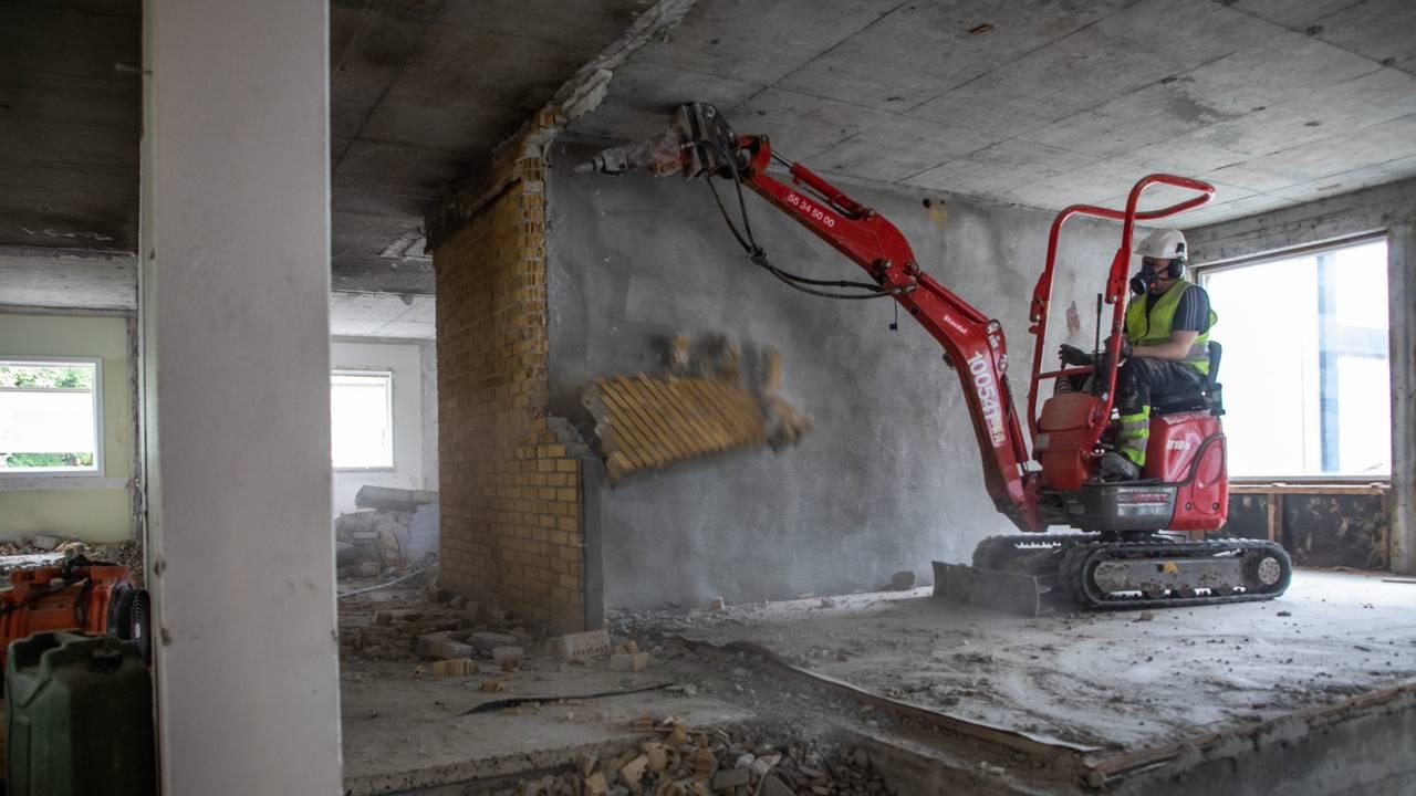 Hele rommet har vegger og tak av betong, med unntak av den siste mursteinsveggen. Vi ser at den rives ved hjelp av maskin, som styres av en av rivearbeiderne. Det ligner en liten gravemaskin, men tuppen har et bor som gjør at flak av murstein løsner og treffer gulvet. I en trapp foran maskinen ligger det knust murstein.