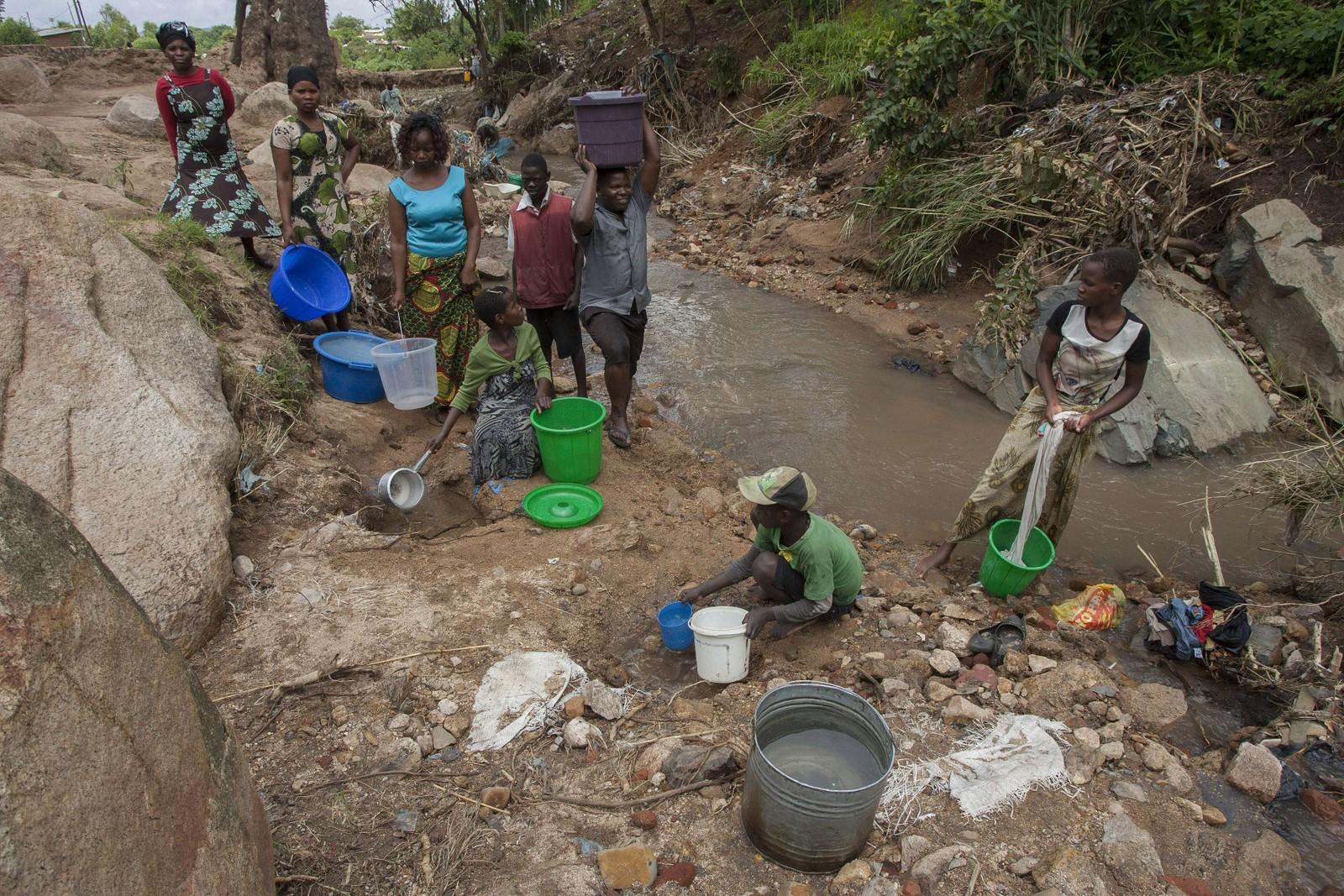 En gruppe kvinner vasker klærne sine i en elv av flomvann.