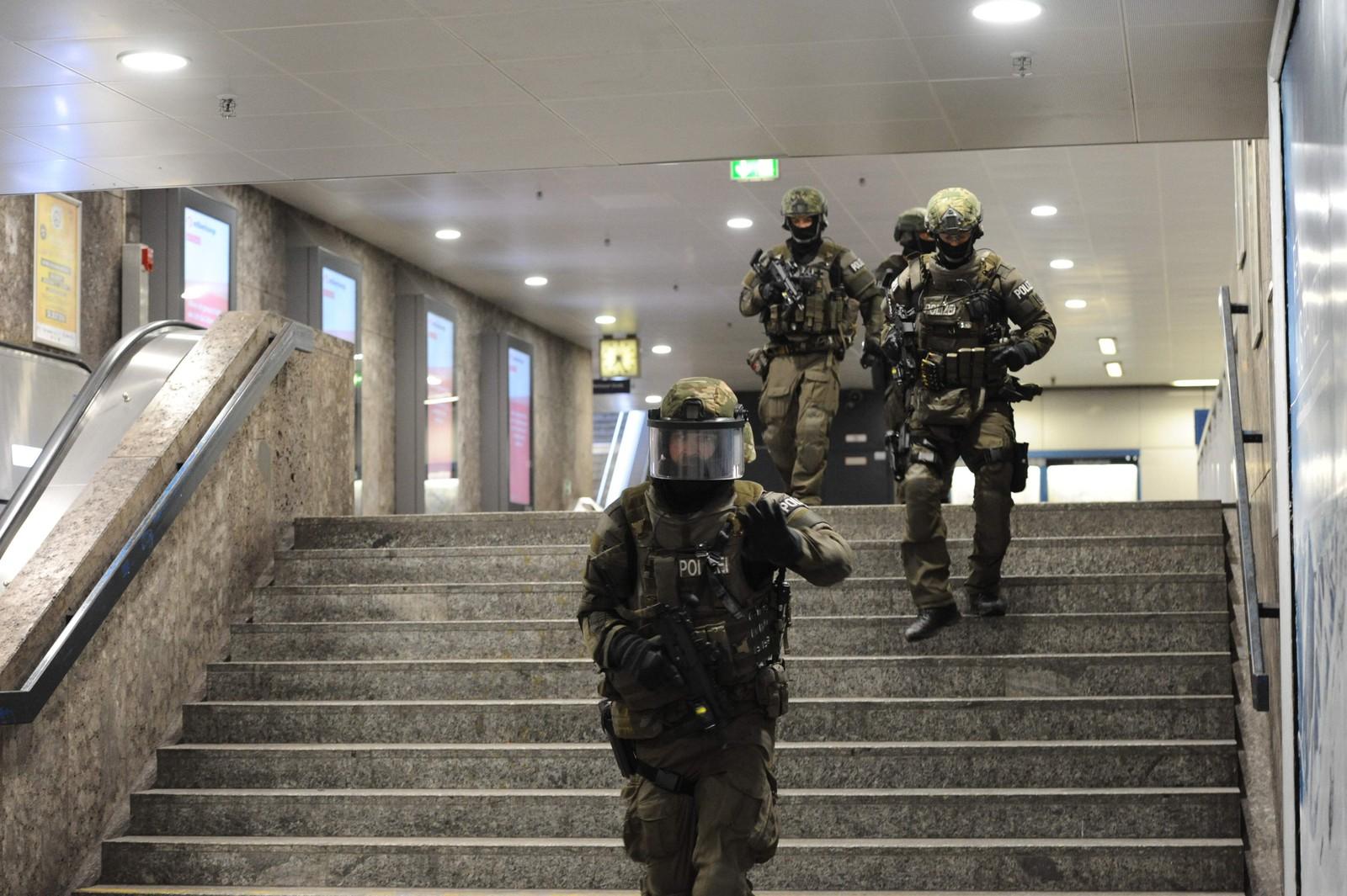 LETER ETTER GJERNINGSMANNEN: Politi sikrer området inne på undergrunnsstasjonen Karlsplatz, i nærheten av kjøpesenteret der minst tre personer ble drept fredag kveld. Gjerningspersonen er ikke tatt.