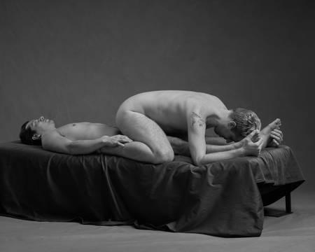 En naken mann ligger på ryggen i senga mens han holder en anen naken mann på leggen som sitter over ham med hodet ned mot føttene hans