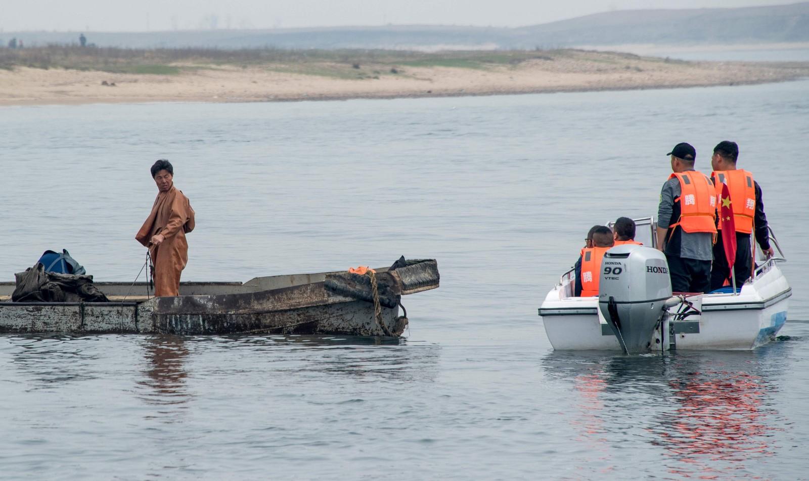 Kinesiske turister ser på en nordkoreansk fisker.