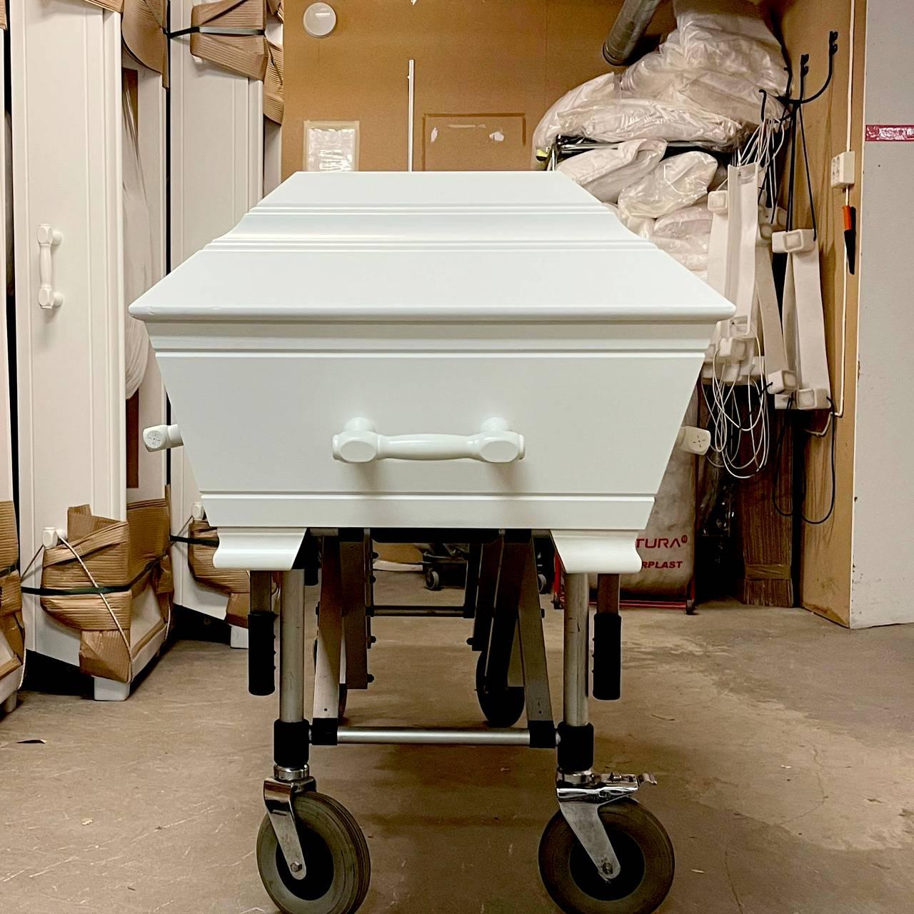 En normal hvit likkiste står på ei tralle med hjul nede i kjelleren til Svanholm og Vigdal gravferd, hvor de har lageret sitt med kister. De står stablet langs veggene.