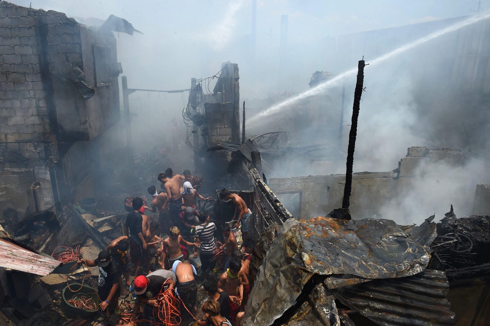 Mennesker kjemper mot hverandre i røyken etter en brann i Manila på Filippinene. De kjemper om å få med seg ting som kan selges senere. 30 hus skal ha brent ned.