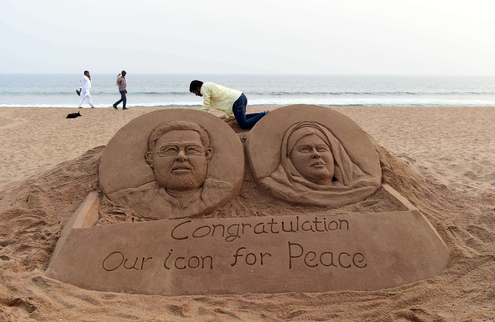 INDIA: Indian sand sculptor artist Sudarshan Patnaik gives the final touches to a sand sculpture showing joint Nobel prize winners, Indian Kailash Satyarthi (L) and Pakistan Malala Yousufzai on the beach in Puri, on December 10, 2014. Pakistani schoolgirl Malala Yousafzai received the Nobel Peace Prize on December 10 in Oslo, Norway as the youngest ever laureate, sharing her award with Indian child rights campaigner Kailash Satyarthi.