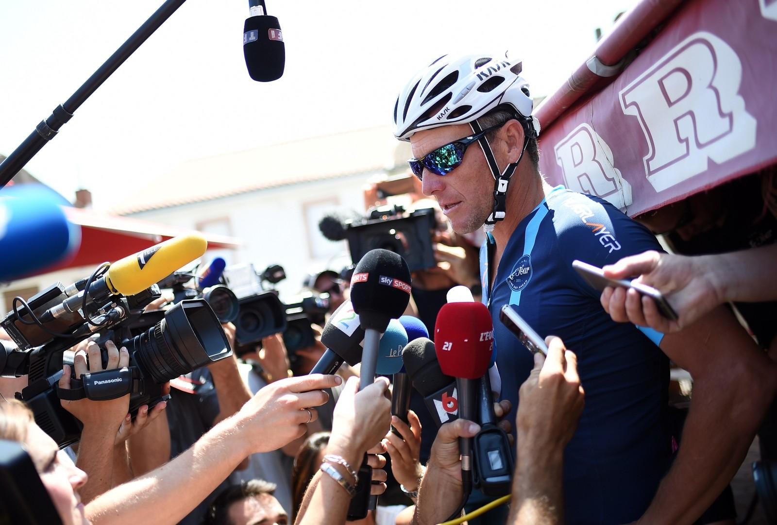 Lance Armstrong dukket opp - og utløste nesten slåsskamp blant fotografer og journalister som alle ville ha den beste intervjuposisjonen. AFP PHOTO / STEPHANE DE SAKUTIN