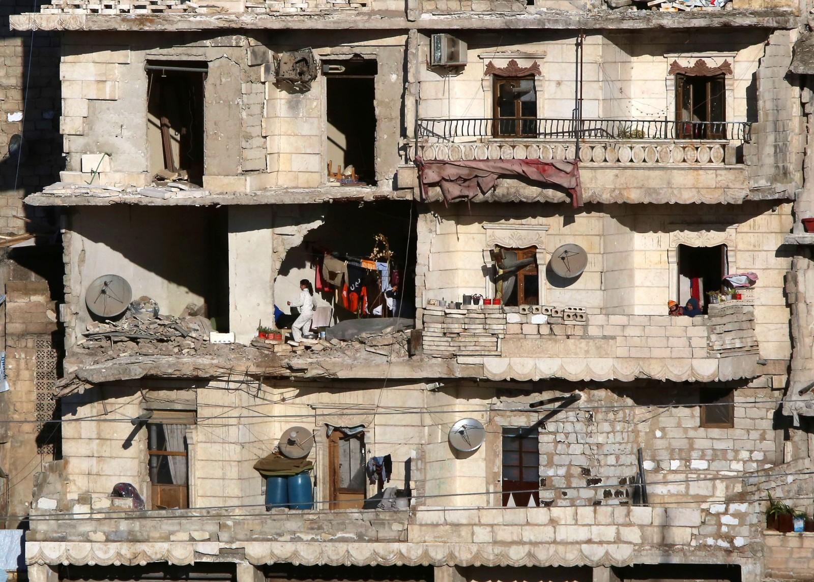 Innbyggere i et sønderbombet hus i en regimekontrollert del av Aleppo.