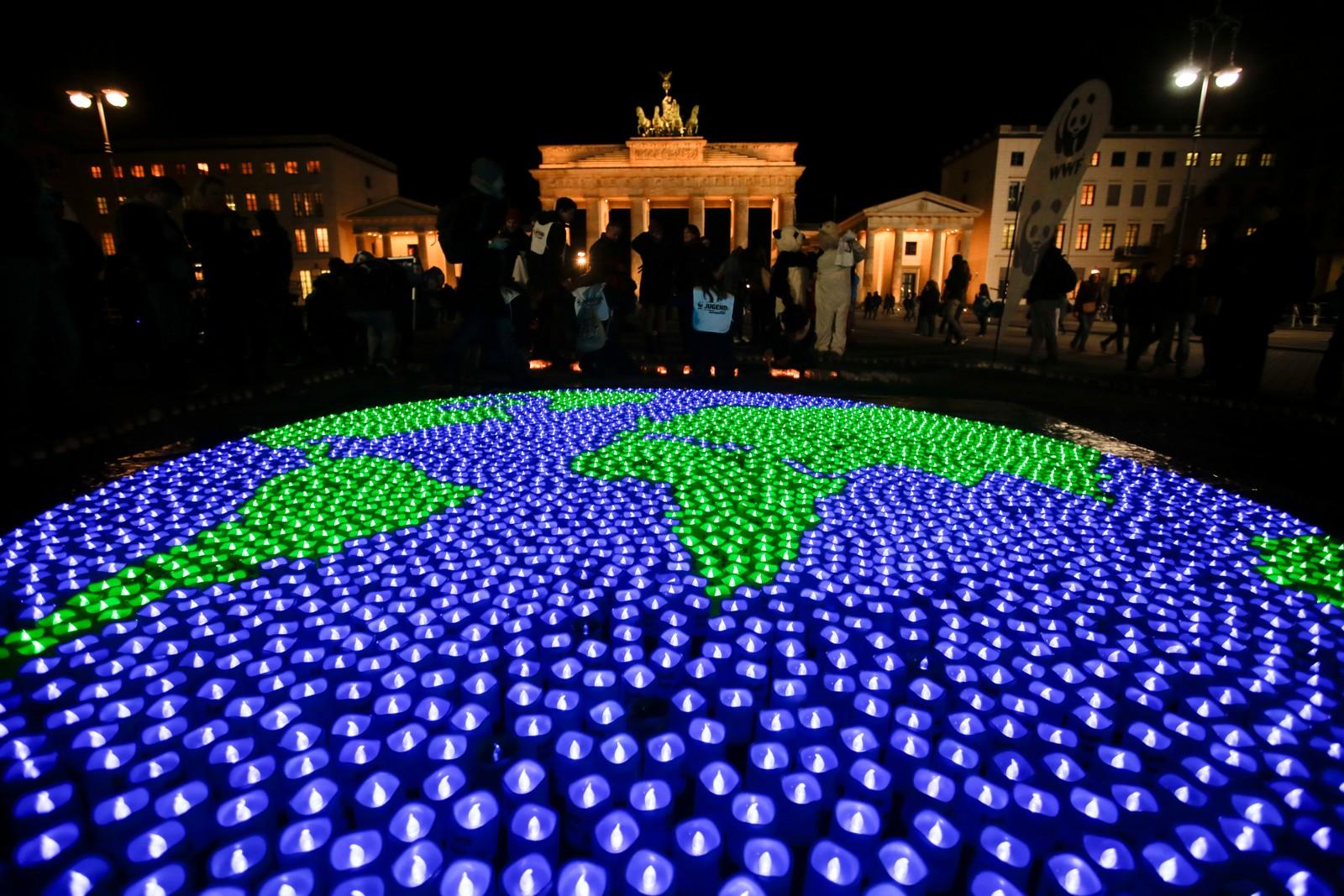Aktivister feirer på Brandenburg Tor i Berlin like før lysene slukkes i Tyskland.