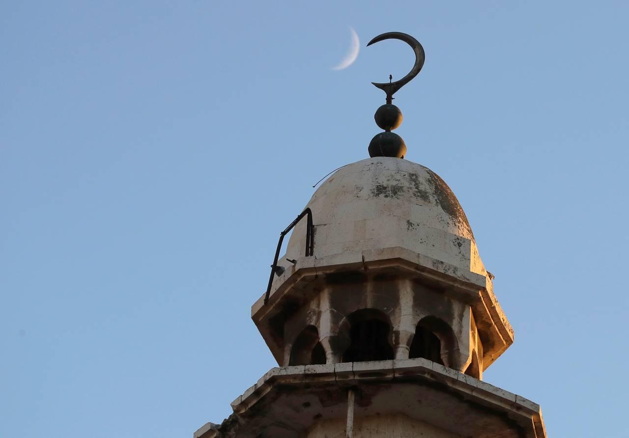 Månen synlig over moskekuppel