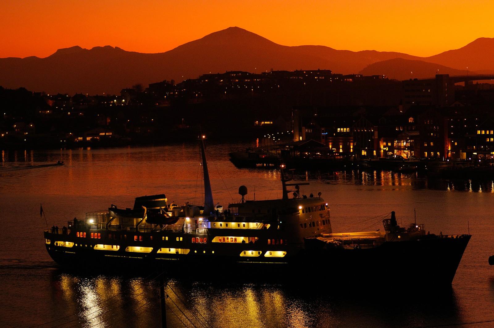 Hurtiguta Lofoten kommer til kai på havna i Kristiansund etter solnedgang.