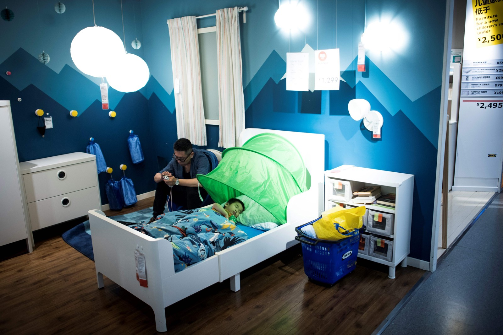 """Far og sønn flykta fra varmen og """"tok inn"""" på Ikea i Shanghai denne uka. Gradestokken skal ha nærma seg de øvre delene av 30-tallet."""