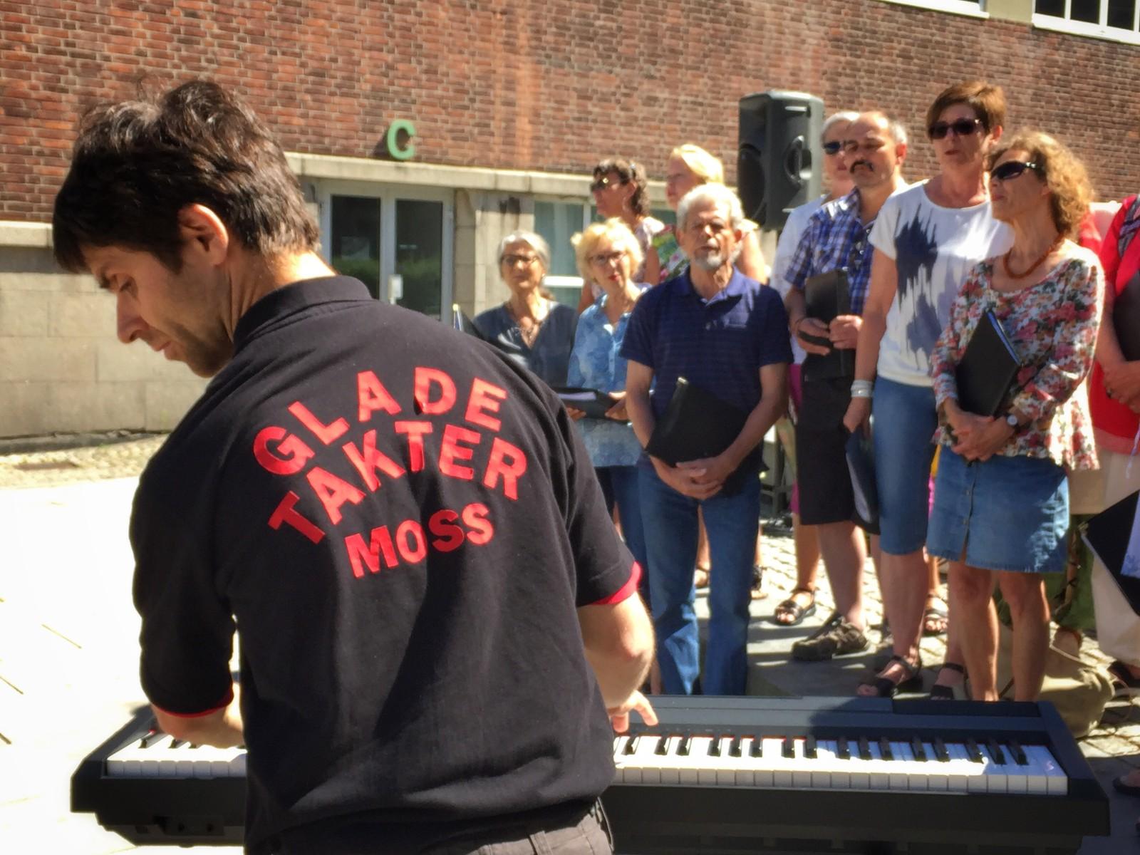 Det kommunale koret Glade Takter varmer opp til utekonsert ved Kirkeparken VGS.