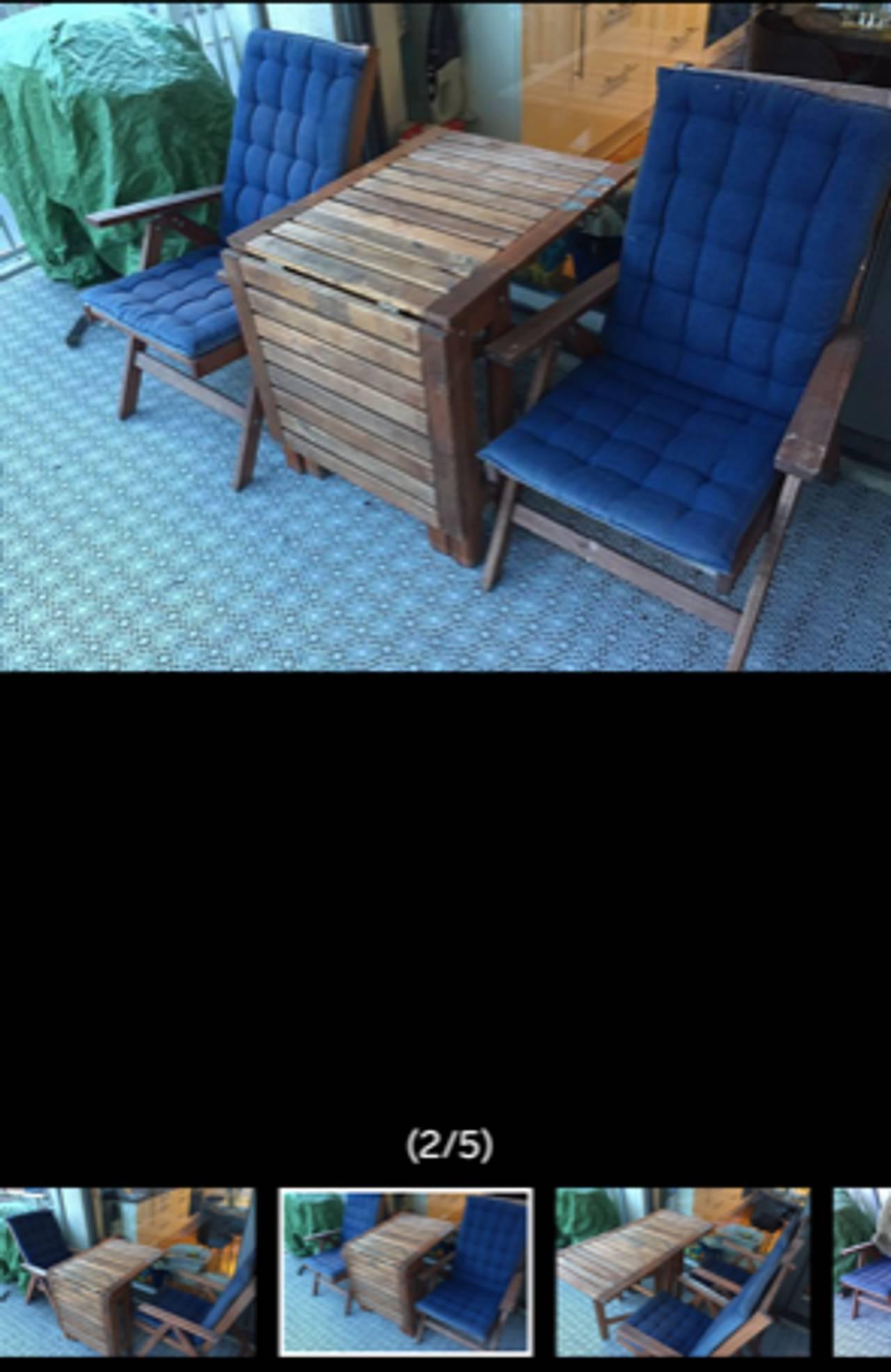 Brune hagemøbler med blå puter på en veranda.