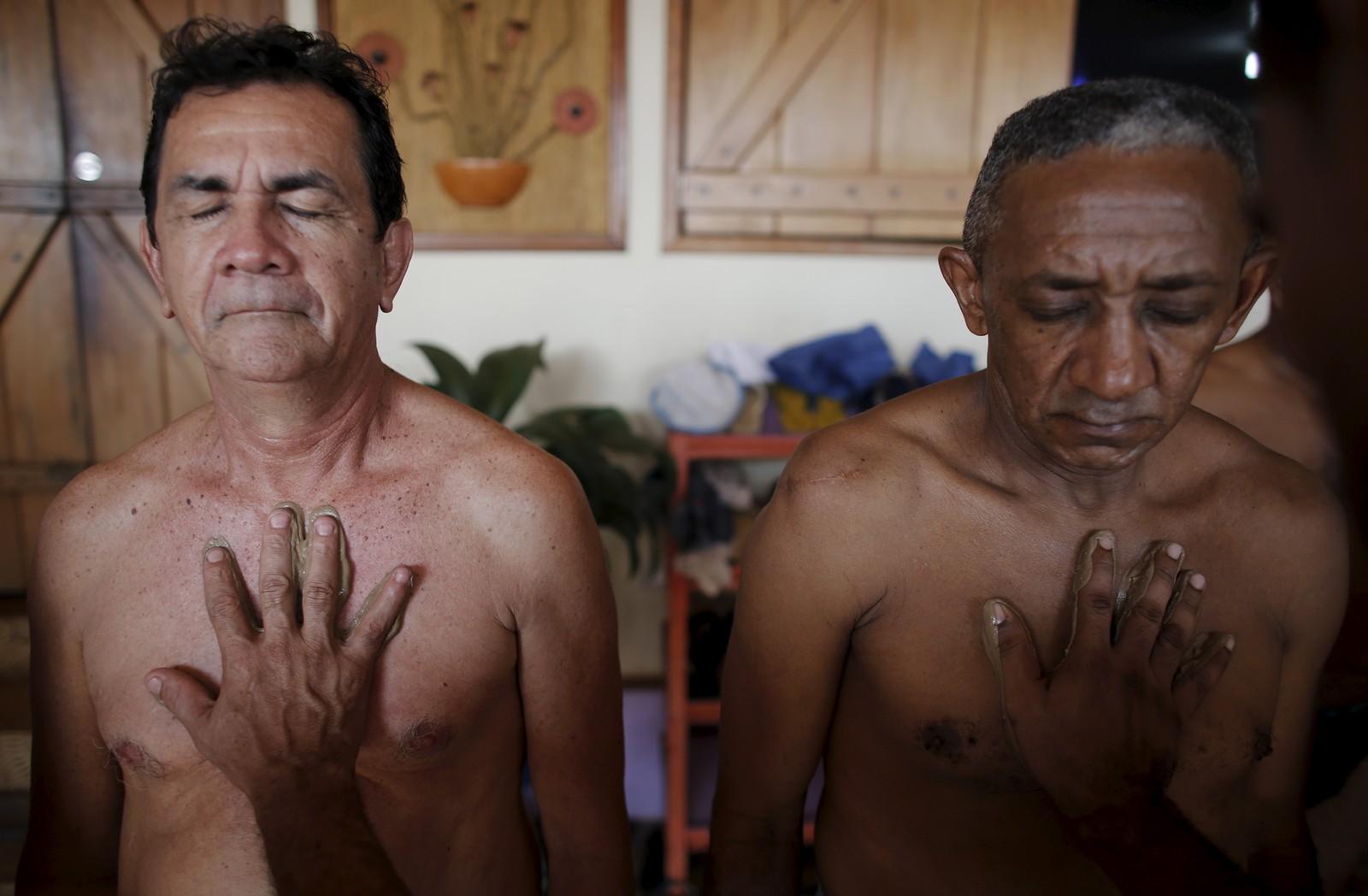 De brasilianske fengselsfangene Helio Steves (til venstre) og Epifacio Soares fotograferes under en gjørmeterapi-time. Fangene tilbringer mye tid i mørke celler, og gjørmeterapien, sponsa av veldedige organisasjoner, skal visstnok være bra for huden.