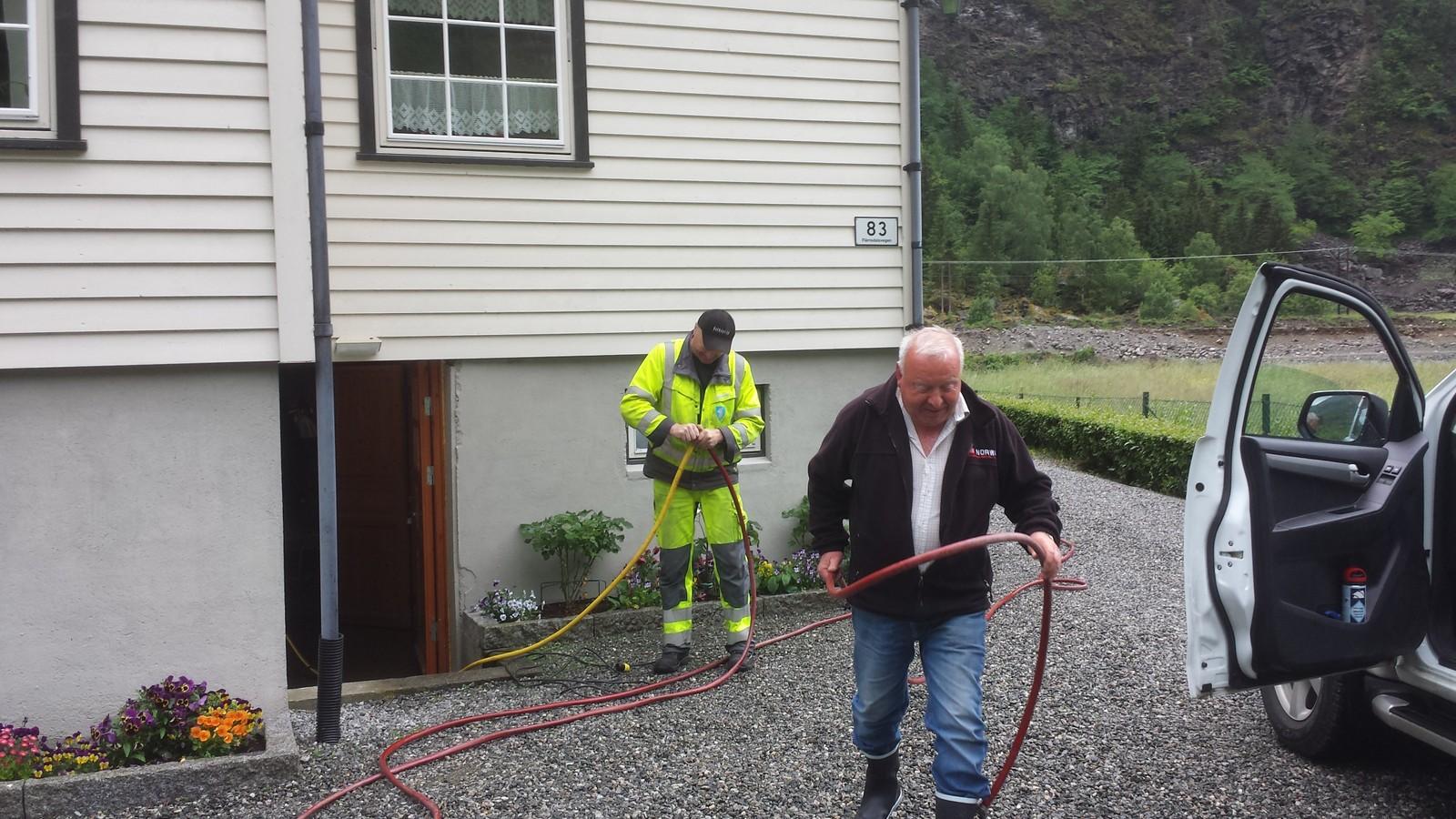 Knut Heggestad får hjelp frå Aurland kommune til å pumpe vatn ut frå kjellaren.