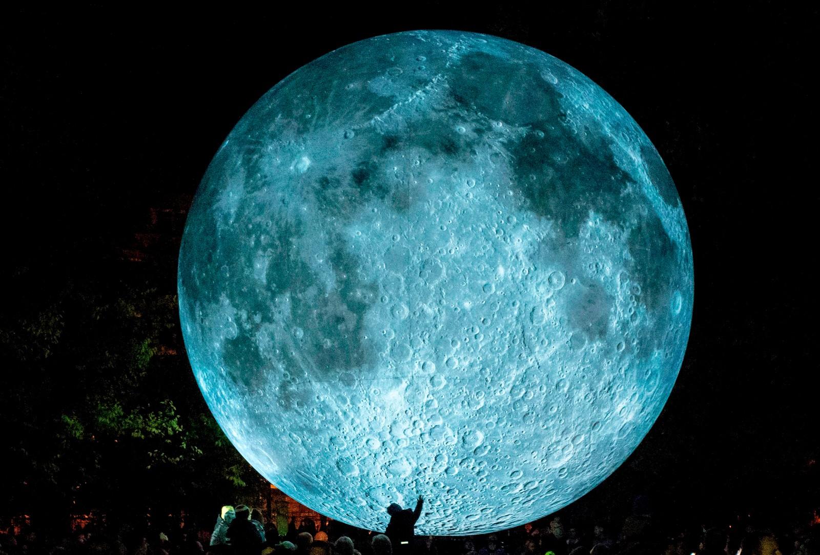"""Et barn tar på en installasjon som heter """"The Museum of the Moon"""" i Bratislava i Slovakia. Det er den britiske kunstneren Luke Jerram som står bak verket."""
