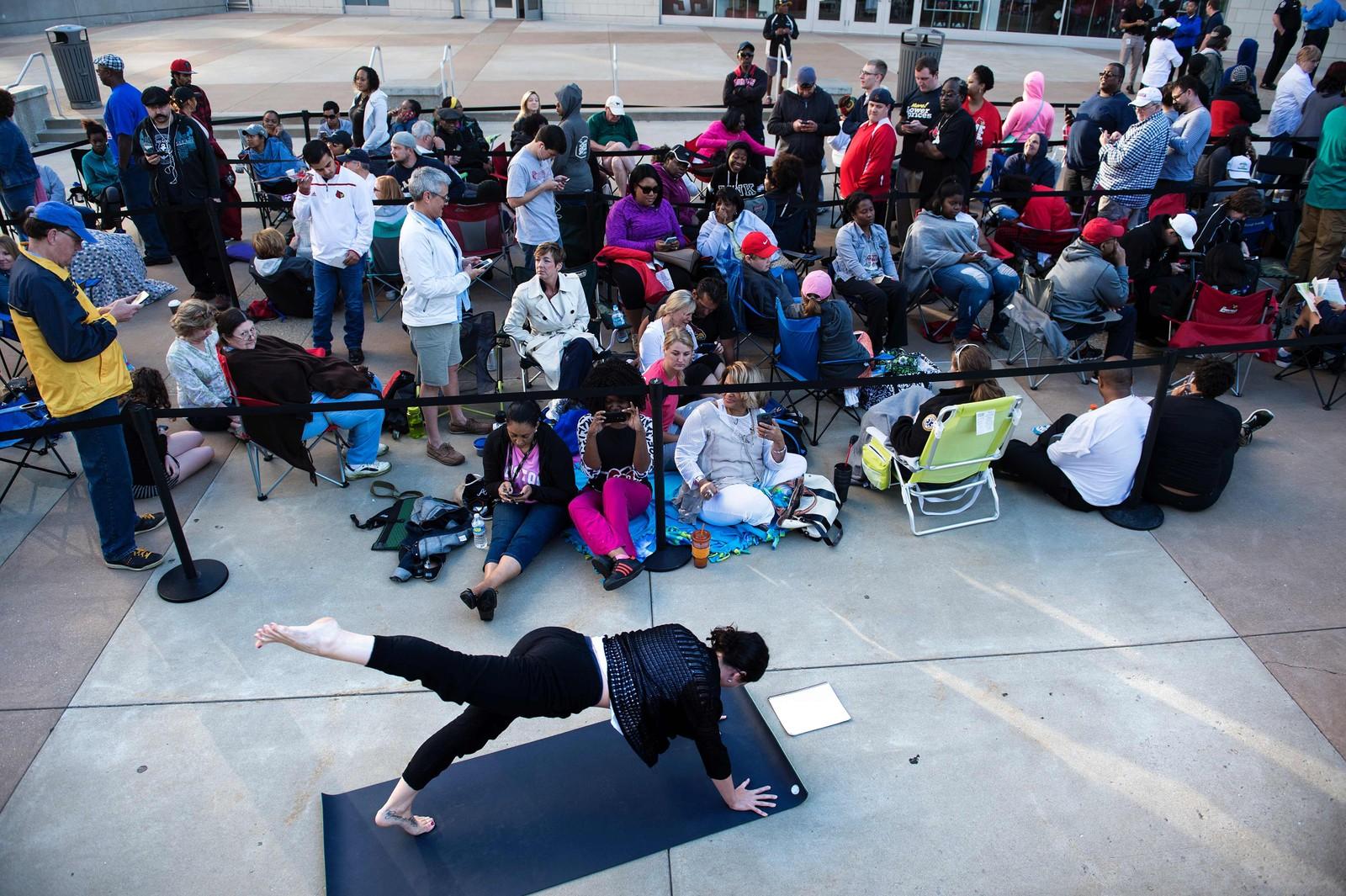 En kvinne gjør yoga mens hun og en rekke andre sto i kø i Louisville, Kentucky for å skaffe seg billett til minnestunden for bokselegenden Muhammed Ali, som døde 3. juni. Han ble 74 år gammel.