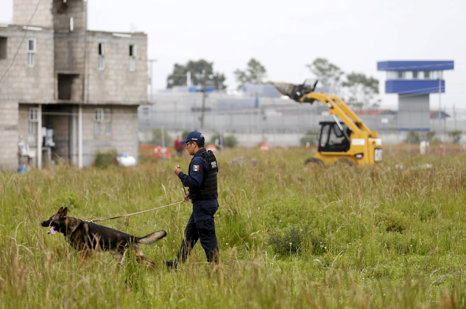 En politipatrulje med hunder leter etter spor utenfor Altiplano-fengselet.