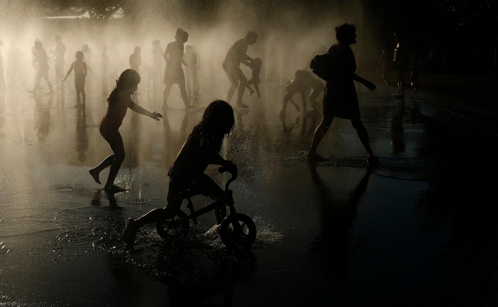 Barna leikar i fontenen som ligg langs Manzanares-elva i Madrid. Det er meldt om døde personar i Spania etter at ei hetebølgje har gått gjennom landet. På det verste har temperaturane vore over 40 grader i skuggen.