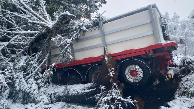 DÅRLIG FØRE: Lastebilsjåføren forsøkte å få ned farten, men skled ut i en sving. Føreren er fraktet til sykehus, og skal ikke være alvorlig skadd.