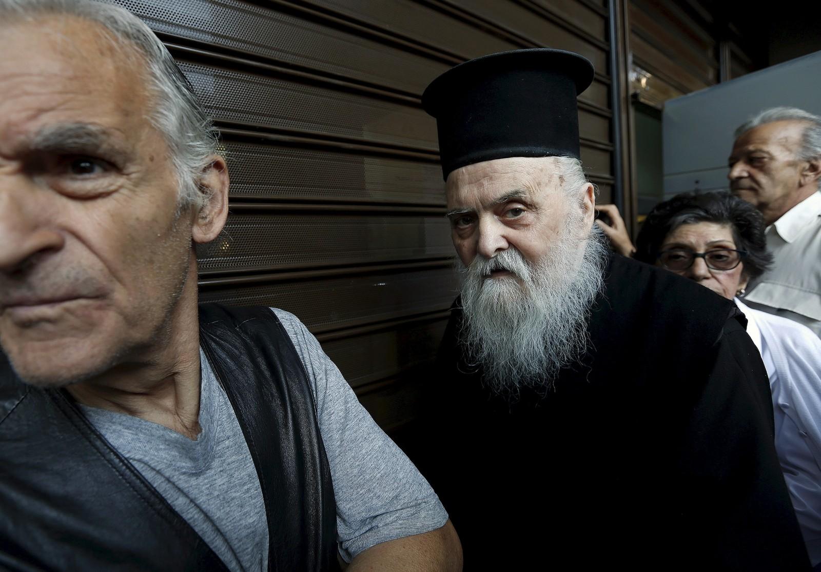 Den gresk-ortodokse presten, fader Theiklitos (77), venter i kø sammen med mange andre pensjonister utenfor en Alpha Bank i Aten.