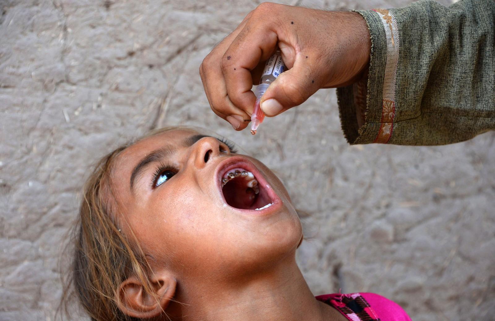 En afghansk helsearbeider gir en jente poliovaksine i Nangarhar den 29. august. Denne dagen satte afghanske myndigheter i gang en vaksineringskampanje som retter seg mot områder som tidligere har vært kontrollert av IS.