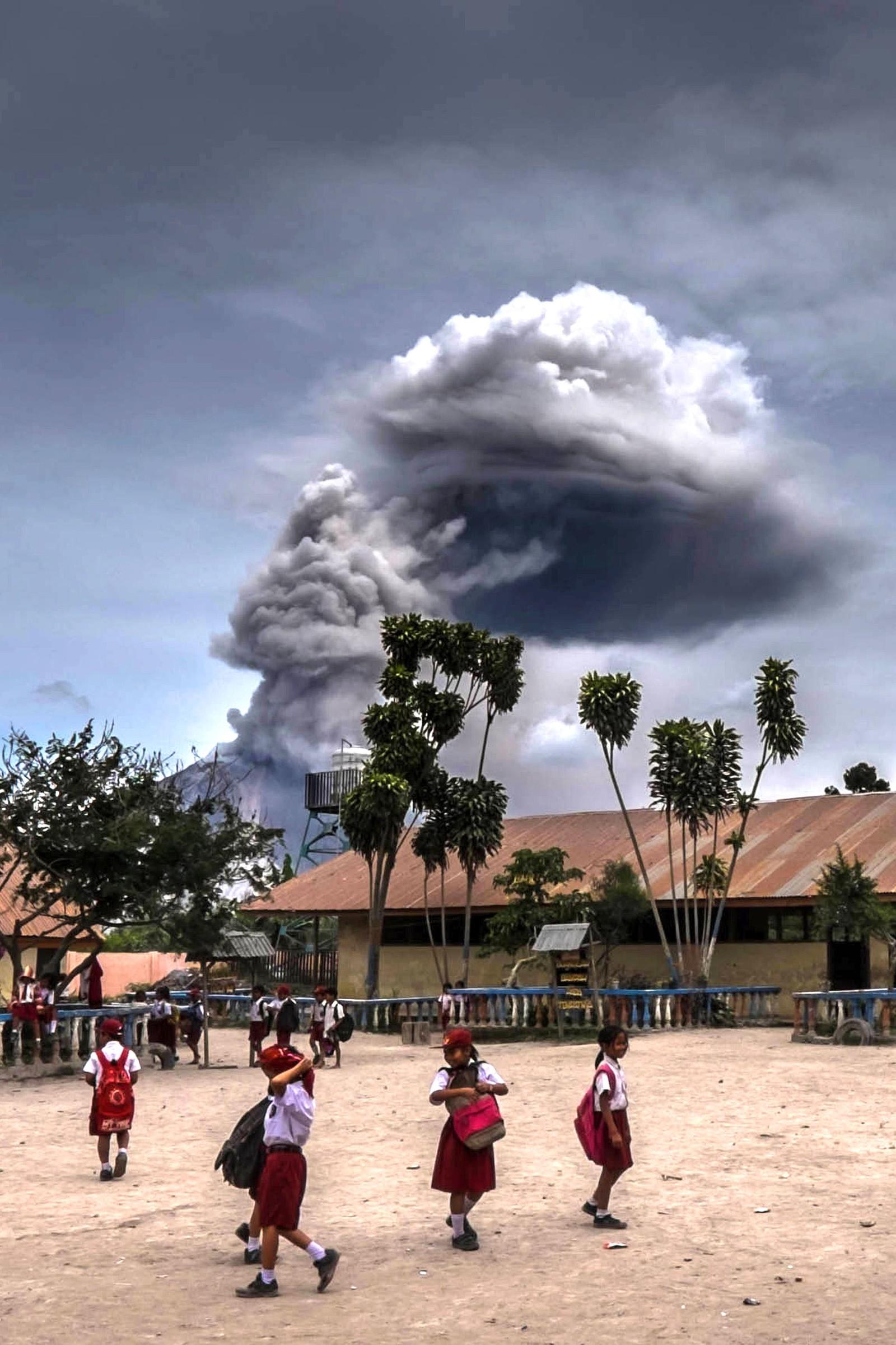 Skolebarn leker mens vulkanen Sinabung spyr ut aske i Karo i Nord-Sumatra den 30. august. Mange mennesker i området har måttet flytte til landsbyer som ansees som trygge. Sinabung er en av de mest aktive vulkanene i Indonesia.