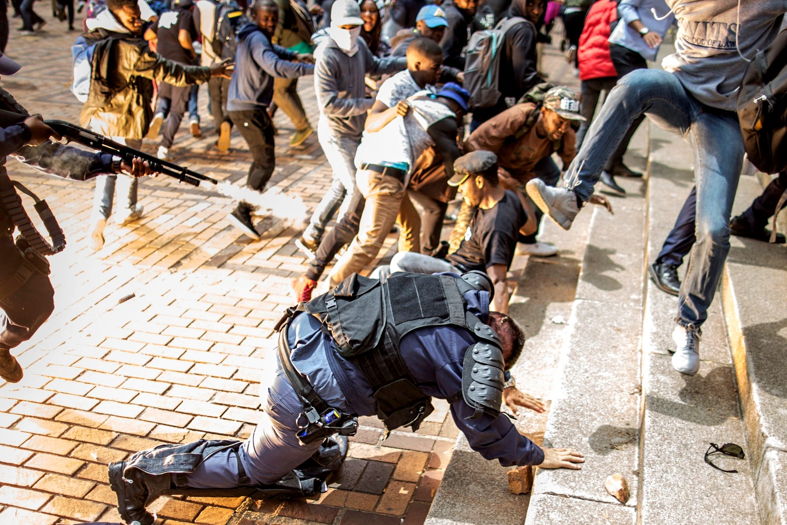 Fullstendig kaos. Studentdemonstrasjonene mot økt studieavgift fortsetter ved Universitetet i Witwatersrand i Johannesburg i Sør-Afrika. Demonstrasjonene har vart i flere uker. Politiet bruket gummikuler, sjokkgranater og tåregass mot studentene.