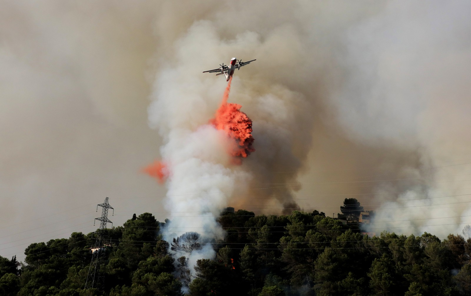 Et fly slipper flammedempende kjemikalier over en skogbrann i en ås nær Nice i Frankrike.