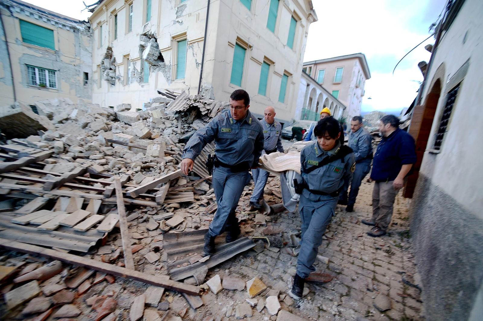 Redningsarbeidere bærer en skadd mann ut av ruinene.