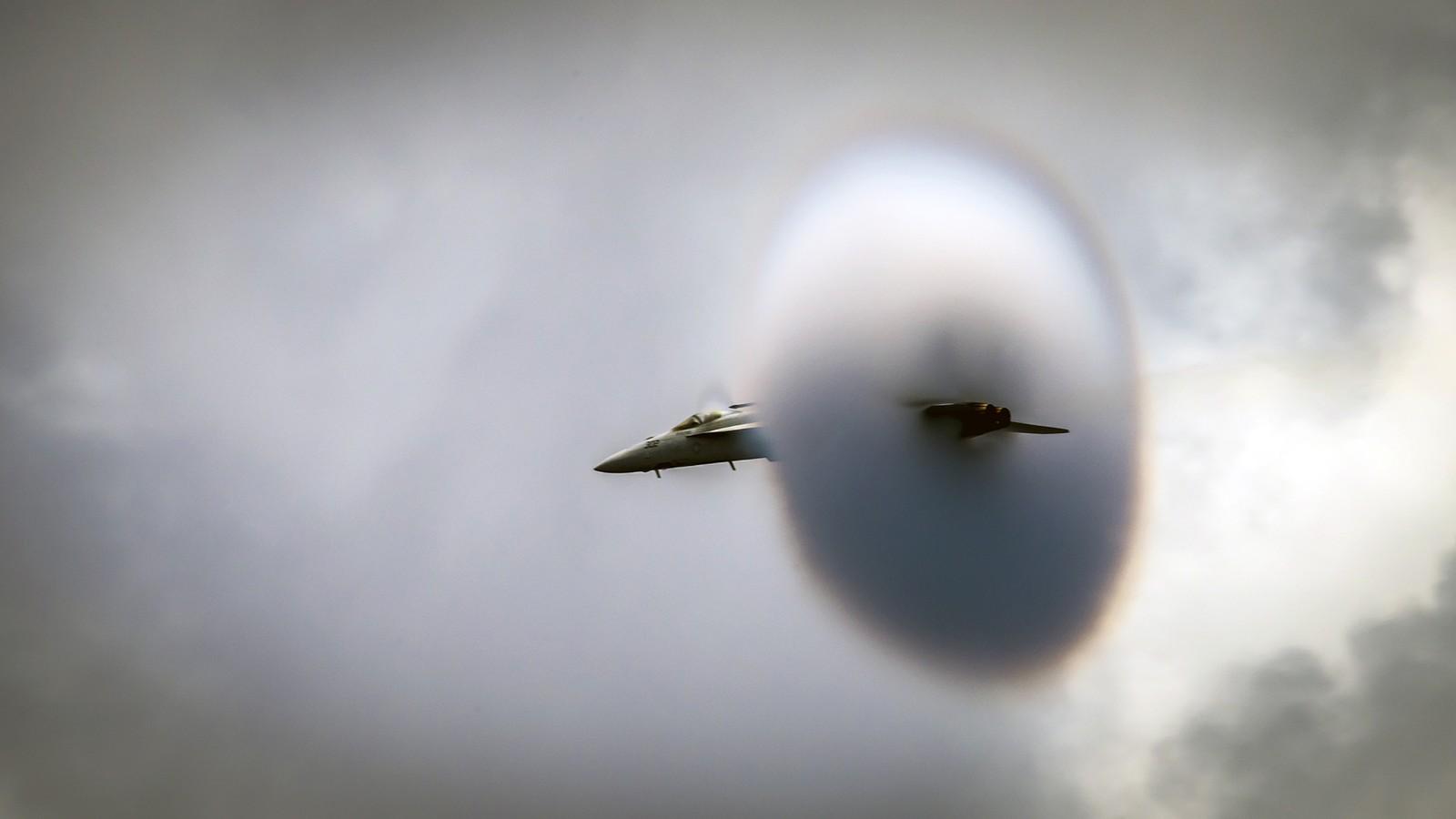 """Et amerikansk jagerfly viser ferdigheter i lufta. Flyet er av typen F/A-18E Super Hornet, og i marinens eget språk kalles det vi ser på bildet for """"a high-speed flyby""""."""