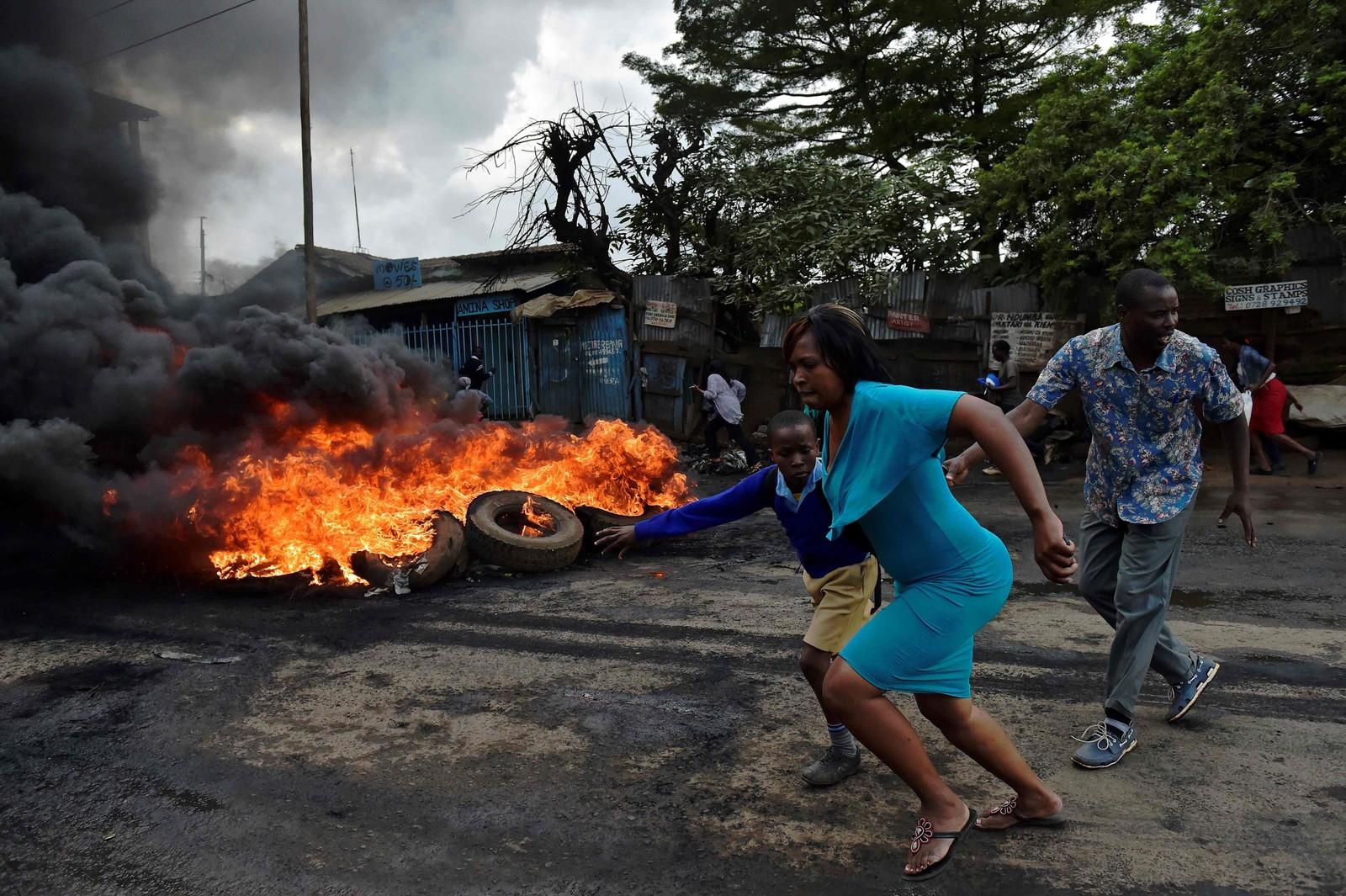 En kvinne river med seg en skoleelev i Kibera-slummen i Nairobi, Kenya under en politisk demonstrasjon.