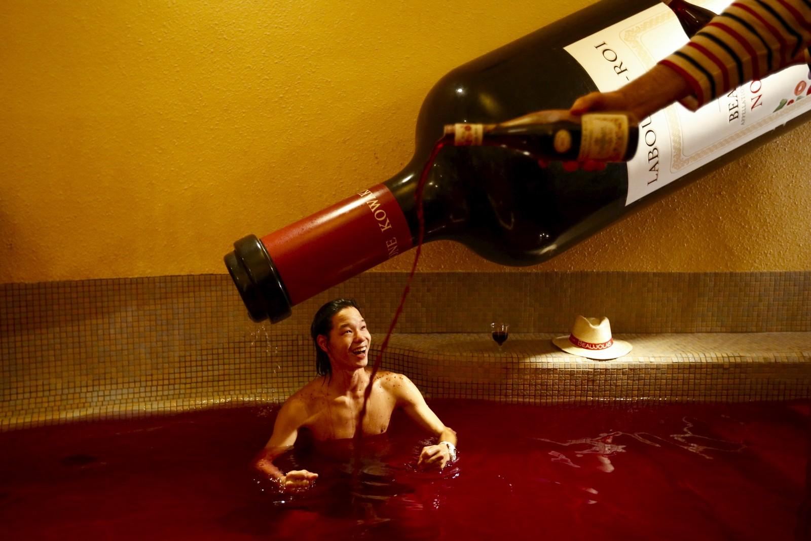 En mann heller vin i et varmt bad med farga vann. Årsaken var feiringen av Beaujolais-dagen i et spa like vest for Tokyo. Om det var innafor å drikke av badet, sier bildeteksten til nyhetsbyrået Reuters ingenting om.
