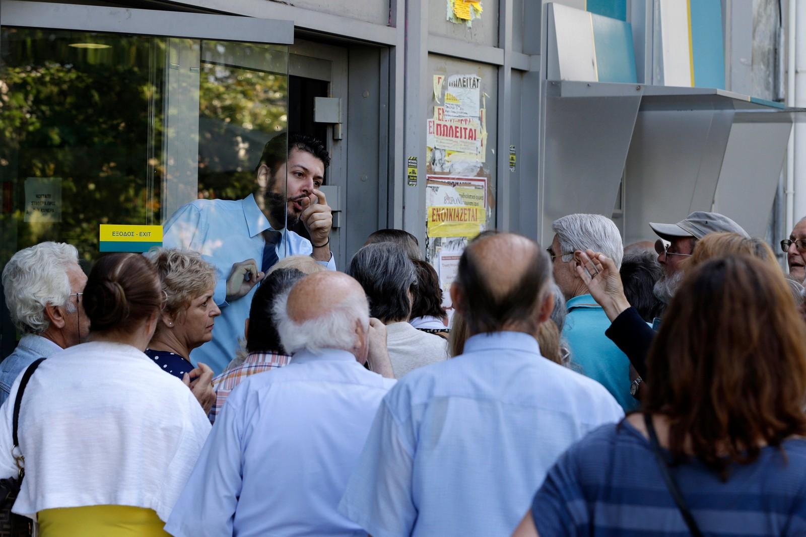 En ansatt gir instrukser til pensjonister som venter utenfor en bank i Aten i Hellas