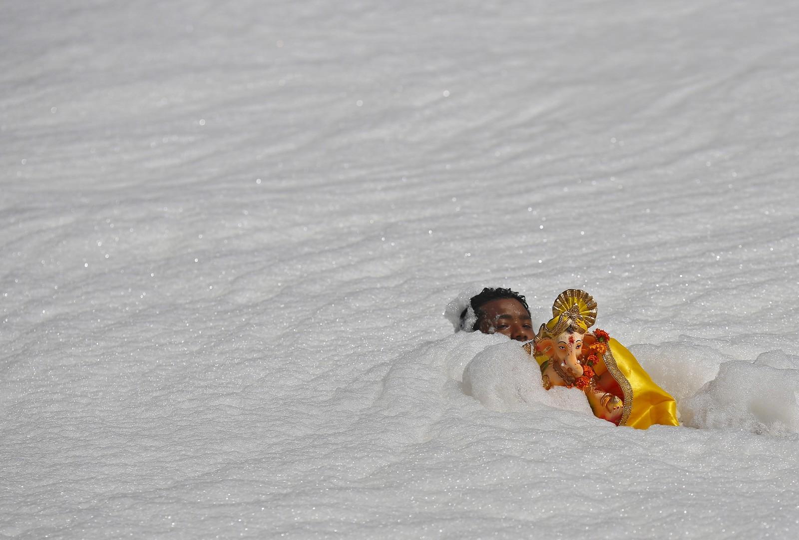 Hindu-guden Ganesh blir båret gjennom et hav av skum, som egentlig er elva Yamuna i New Delhi i forbindelse med en religiøs festival.