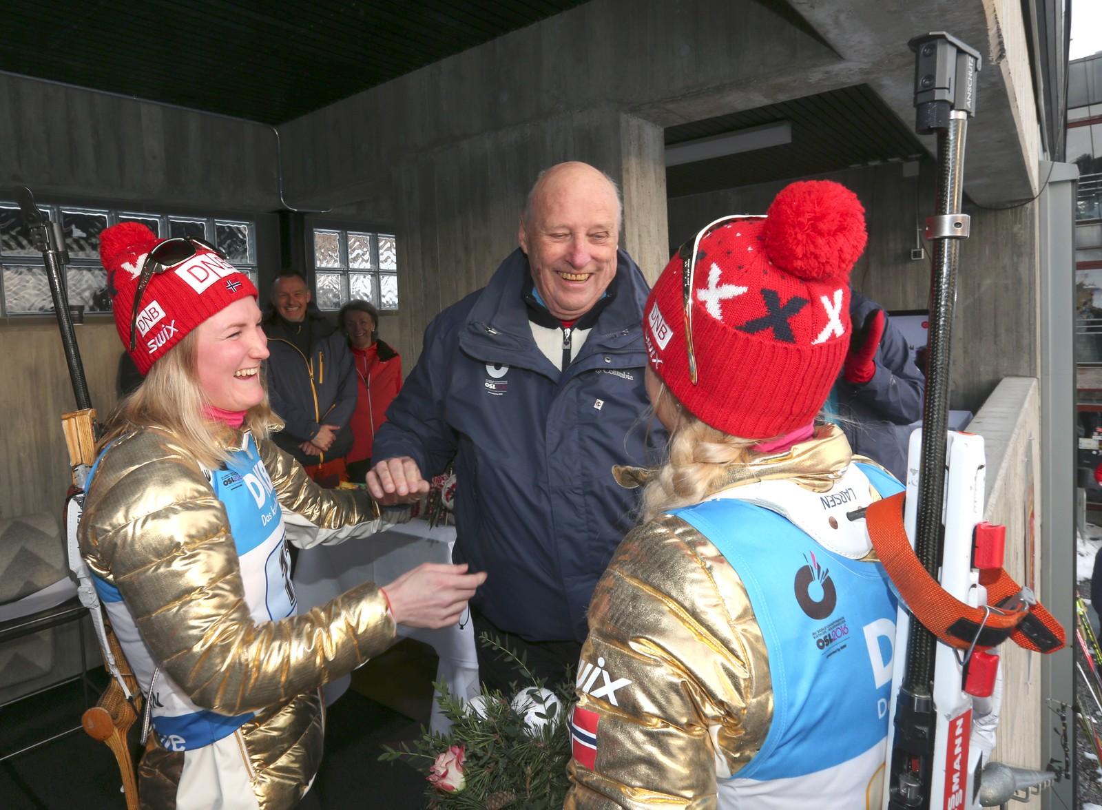 Stafett kvinner VM i skiskyting i Holmenkollen fredag. Kong Harald hilser på Marte Olsbu og Tiril Eckhoff (med ryggen til).