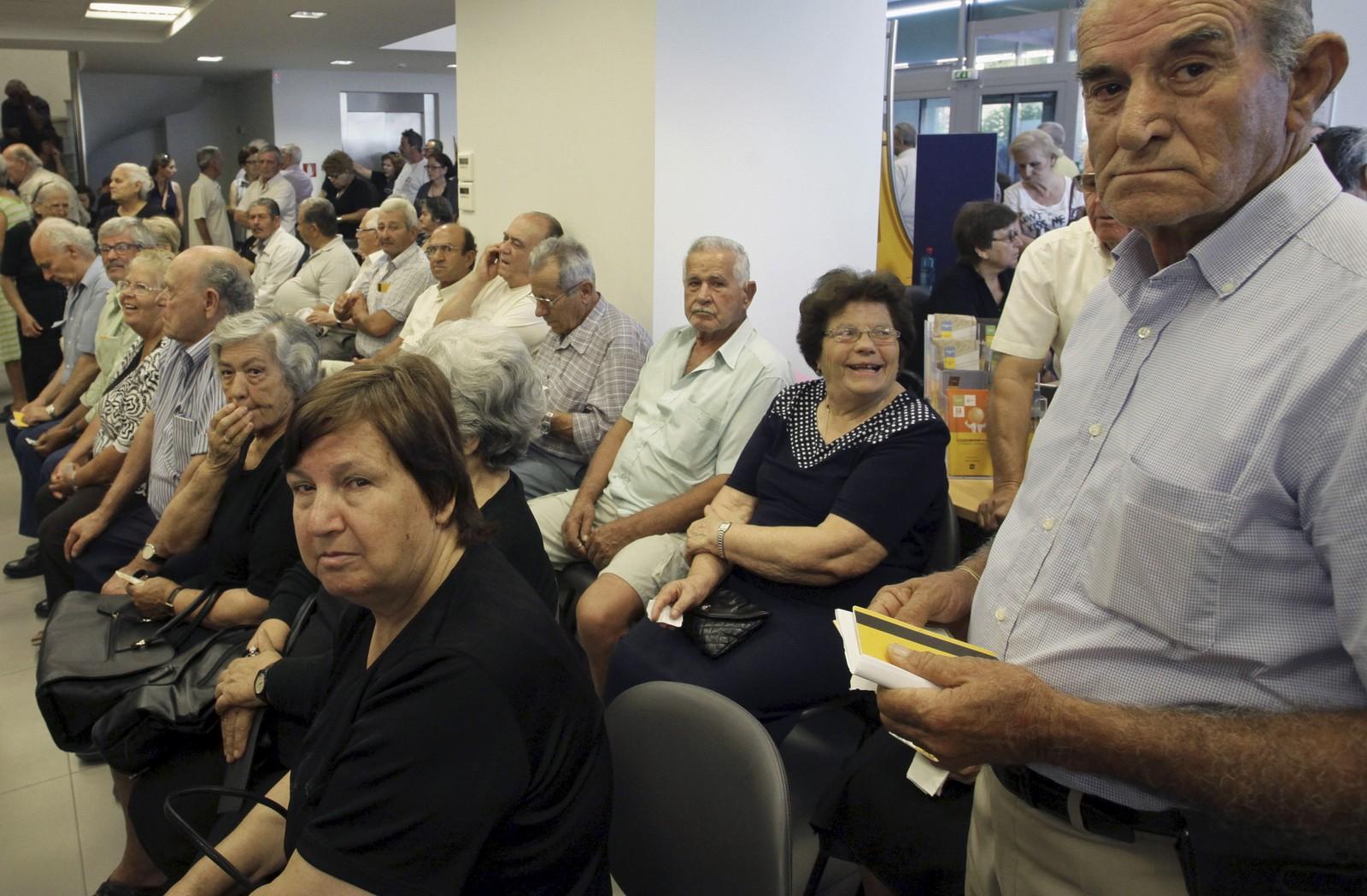 Pensjonister venter inne i en Piraeus Bank i Iraklio på Kreta.