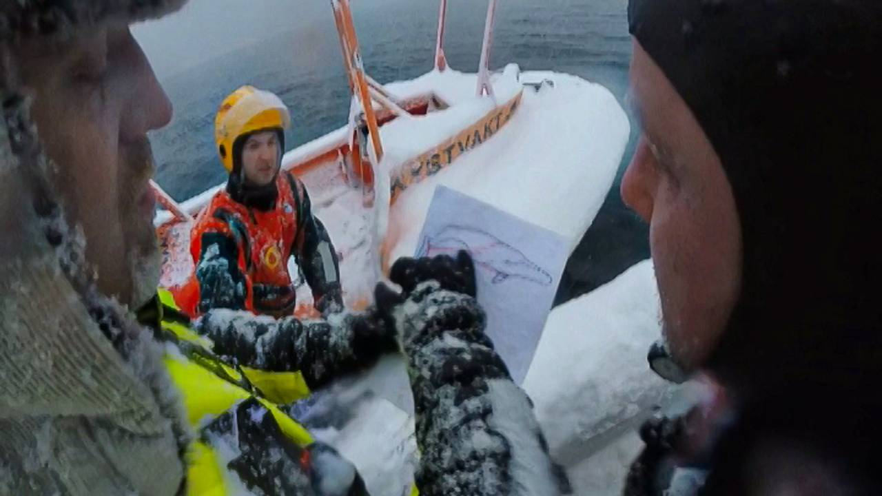 Mannskap fra Tromsø Brann- og redning i båt, ser på tegning av hval som sitter fast