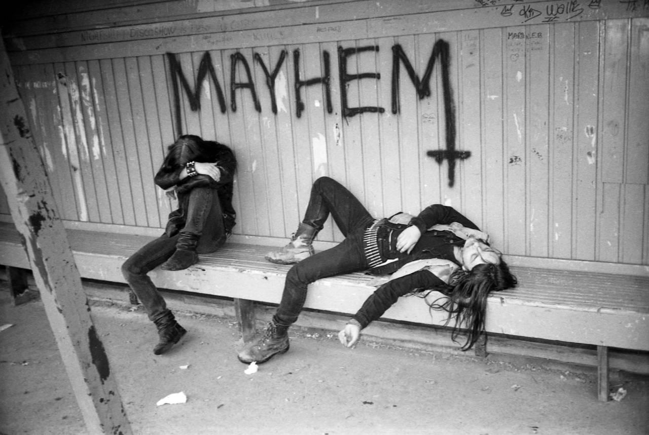 Øystein Aarseth sitter og Jørn Stubberud ligger på en benk på en togstasjon, hvor Mayhem-logoen er tagget på veggen bak dem.
