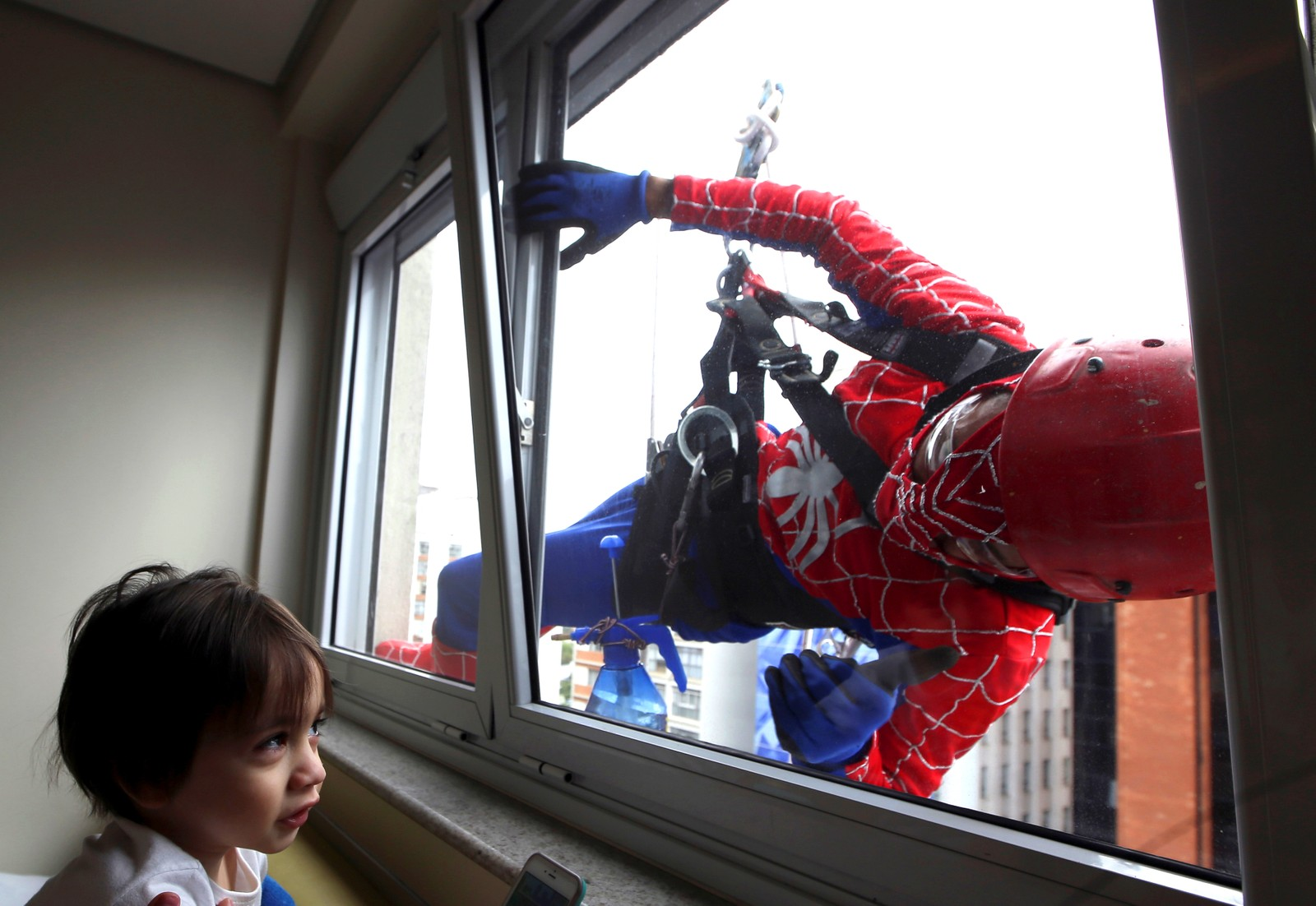 En vindusvasker har kledd seg ut som Spiderman for å underholde Lucas og andre barn ved dette sykehuset i Sao Paulo i Brasil.