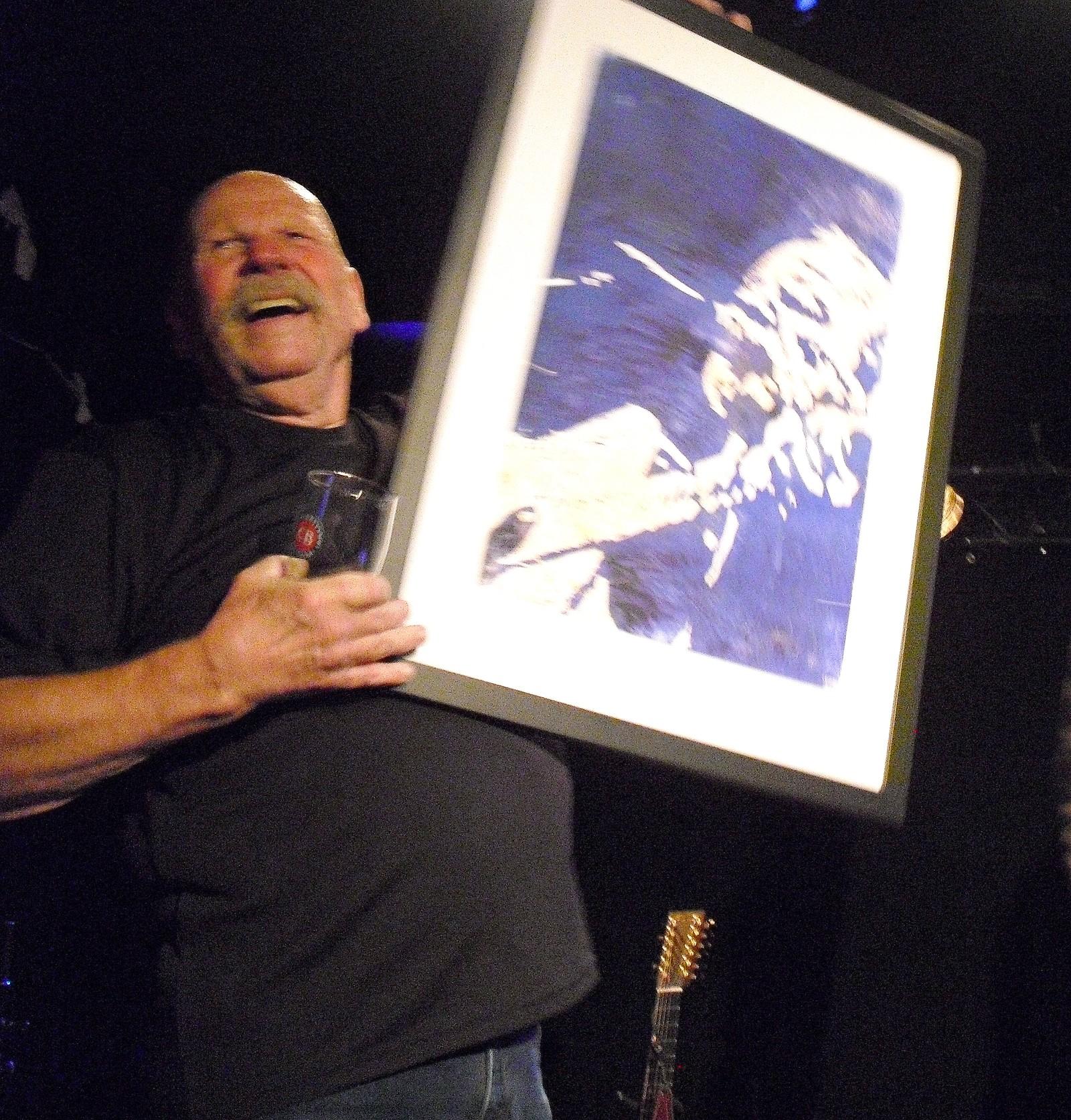 Barry McGuire viser stolt fram portrettet på scena. Laget av Dag Ringstad
