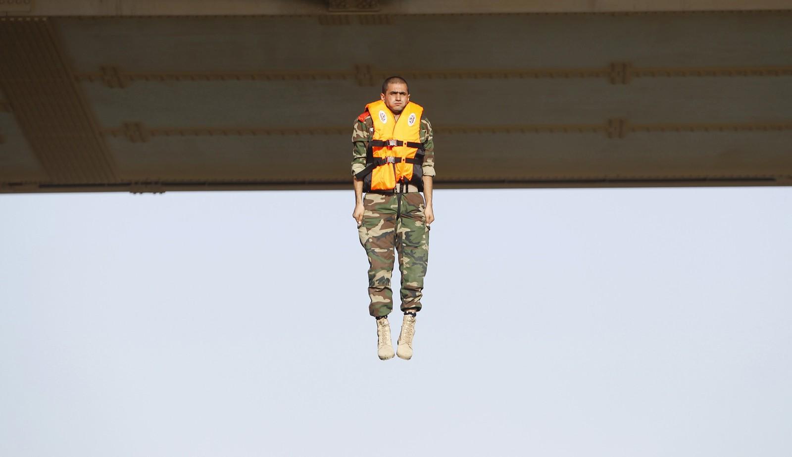 En irakisk soldat utfører det såkalte «the leap of faith» fra en bru i Baghdad.