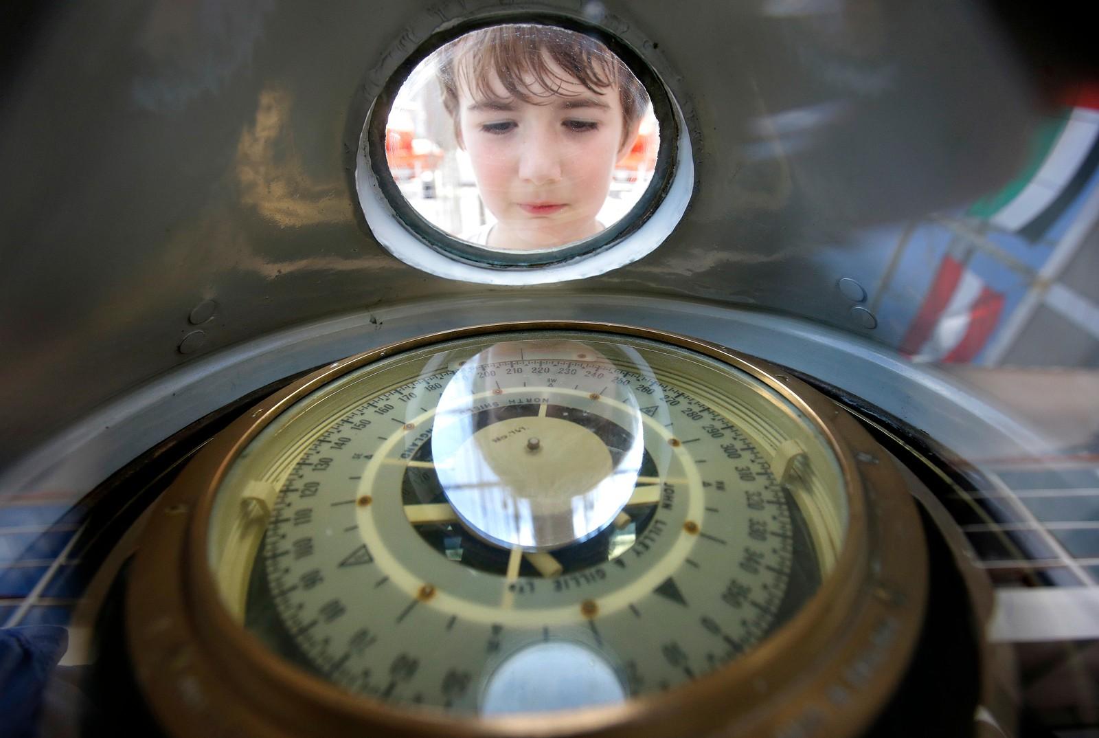 """Åtte år gamle Sean Sullivan tar en kikk på kompasset på et skip under et arrangement som kalles """"Sail Boston"""". Her kunne folk besøke mer enn 50 skip fra Europa, Sør-Amerika og USA."""