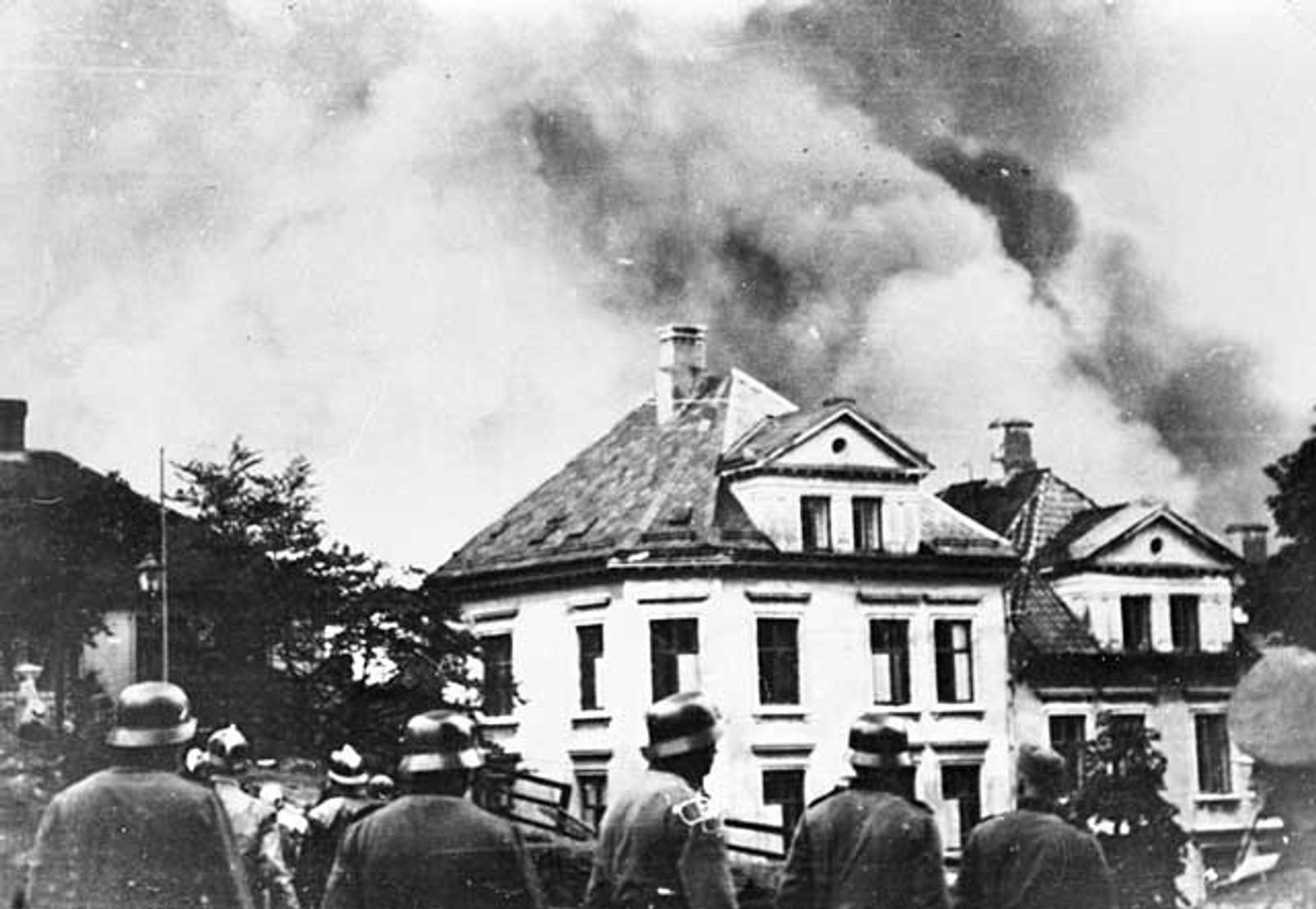BOMBING: Tyske soldater ser på hus som står i brann etter bombeangrep.
