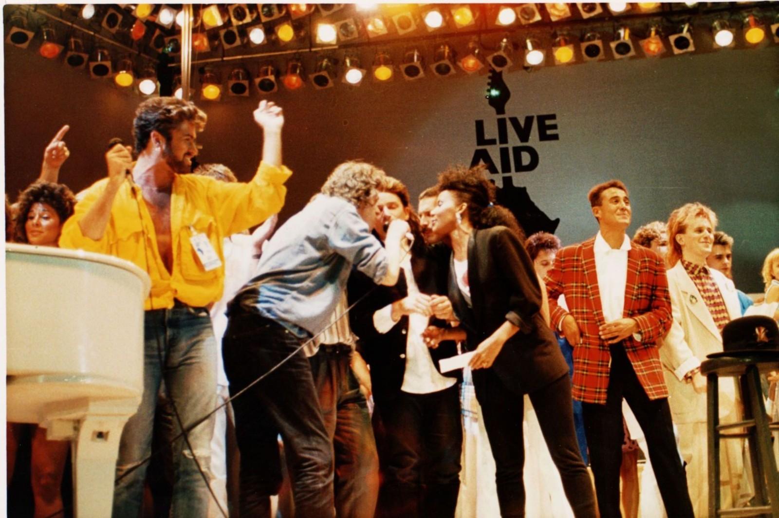 1985: George Michael (i gul skjorte) på scenen under veldedighetskonserten Live Aid på Wembley i London 13. juli 1985. Ellers på scenen: Bob Geldolf, Bono i U2, Freddie Mercury i Queen, Andrew Ridgley i Wham! og Howard Jones.