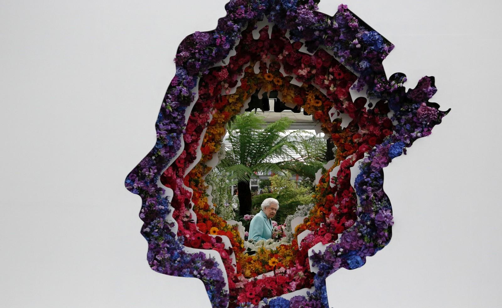 Dronning Elizabeth II sees gjennom en blomsterversjon av henne selv under Chelsea Flower Show i London denne uka.