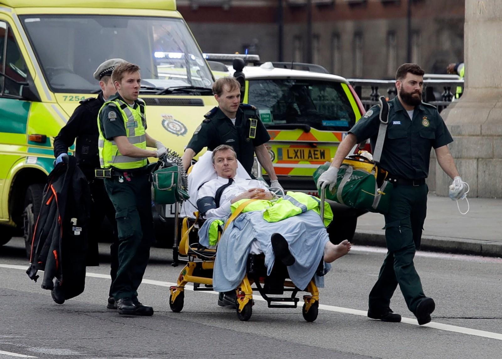 En skadd mann fraktes bort på båre.