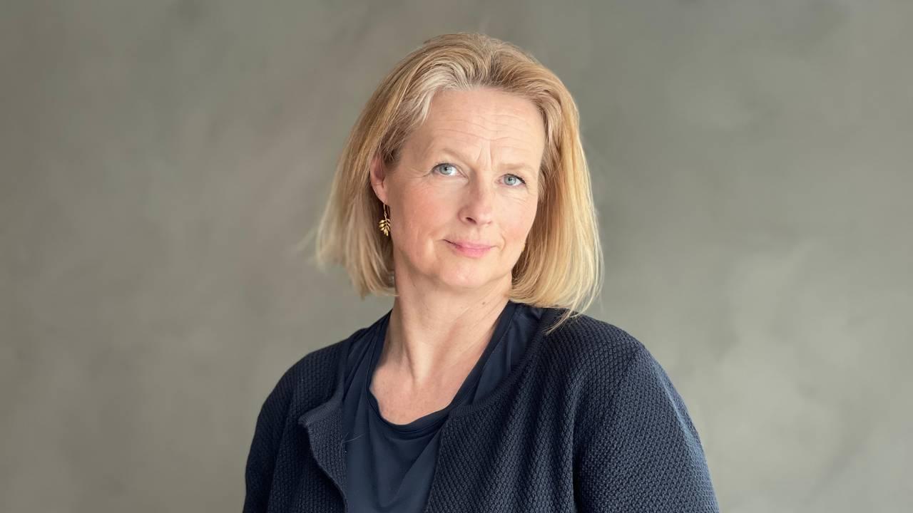 Portrettbilde av statsadvokat Unni Sandøy. Hun er iført marineblå klær, står foran en grå vegg og ser inn i kamera.