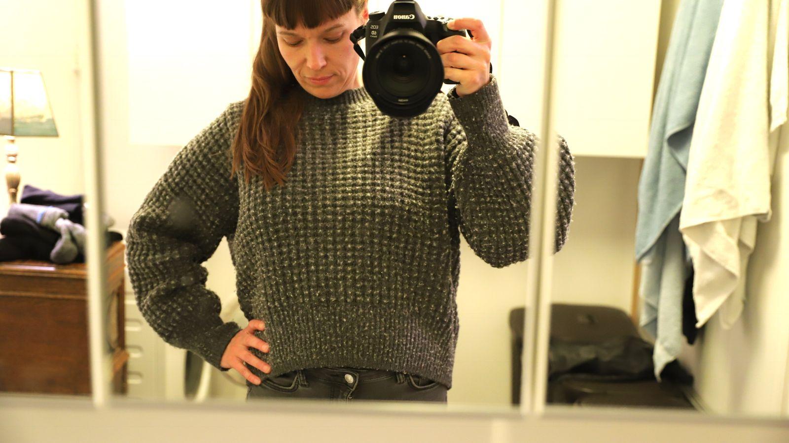 Fotografen tar bilde av seg selv i spelet med en grå, tykk genser på.