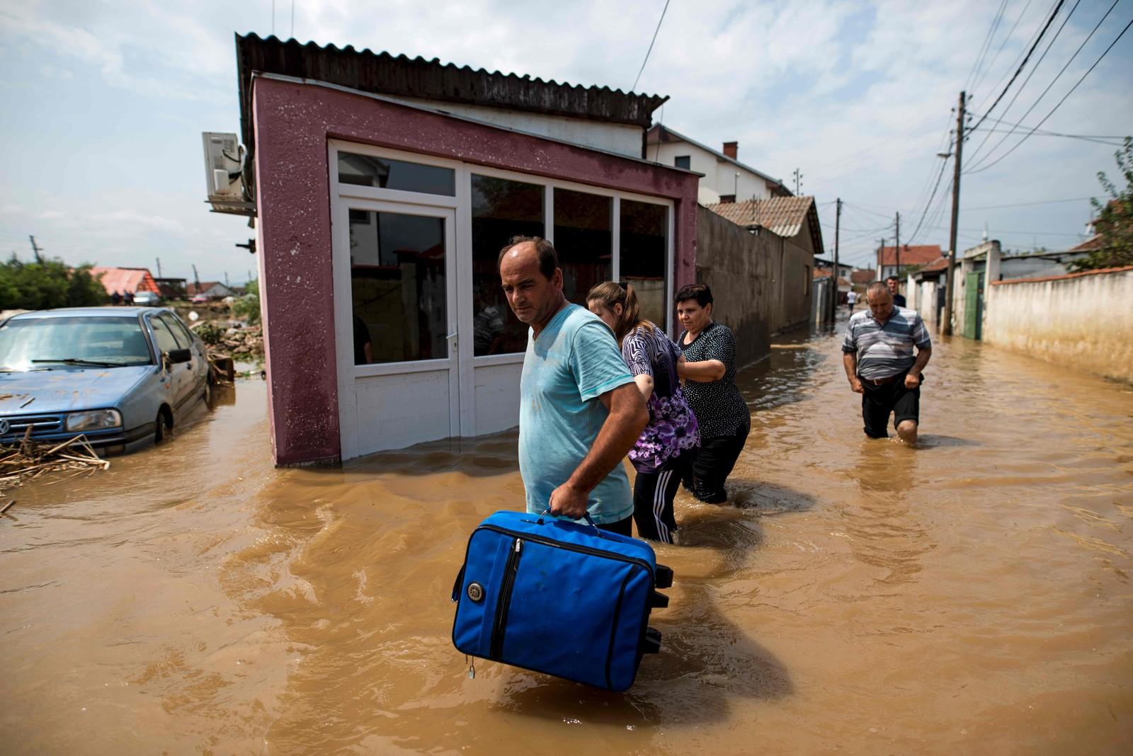 Mennesker drar fra oversvømte hus i Stajkovci.