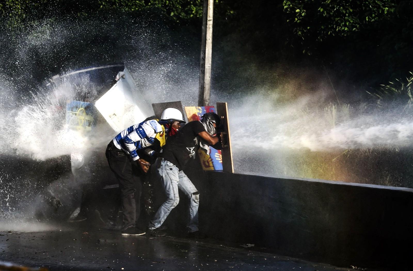 Venezuelanske demonstranter får et vått møte med politiet i Caracas.